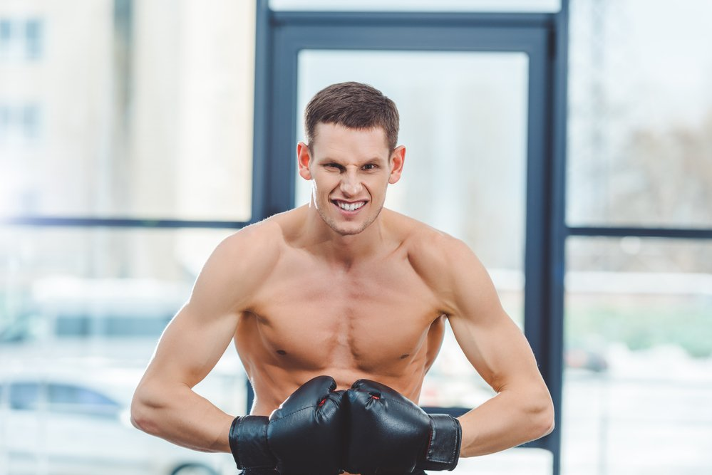 A slim, but fit young man in boxing gloves. He may be a hard gainer.