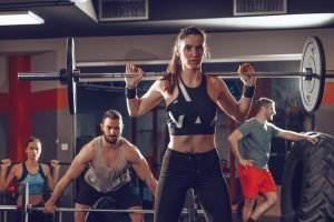 Young muscular woman doing exercise with barbell at the gym. Looking at camera. Behind her there are here friends exercising. Beware of the signs of overtraining