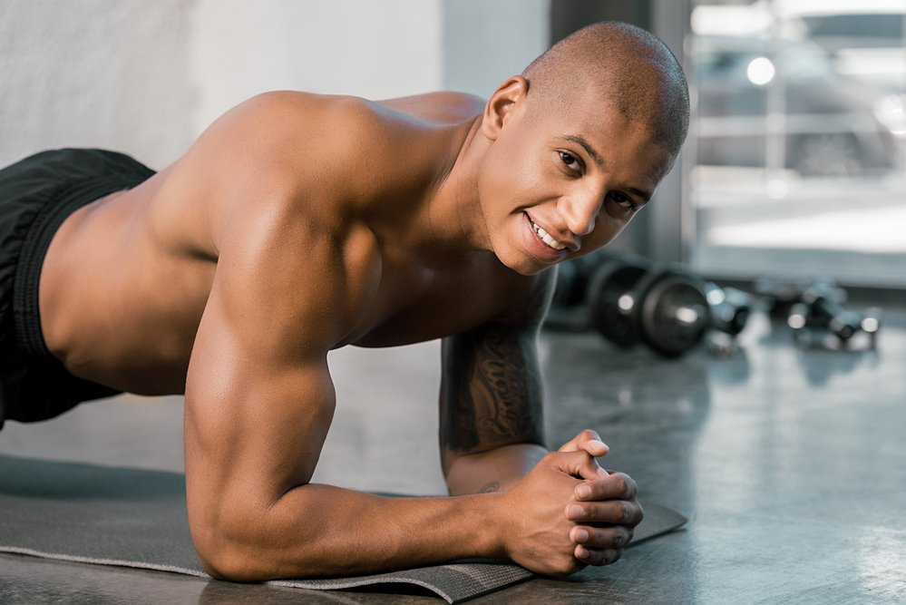 Happy, well-built young man doing a plank in a gym. Gaining lean muscle is hard.