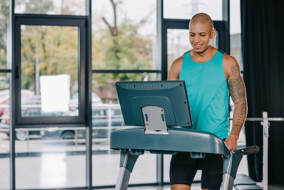 A smiling man enjoying the benefits of cardio by running on a treadmill.
