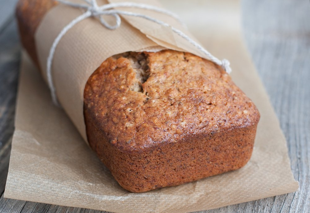 High Protein Banana Bread Loaf, wrapped in brown paper and string, on a wooden table