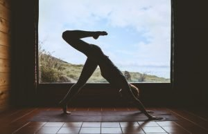 Silhouette of a young woman indoors with a window behind her, doing a vinyasa yoga flow