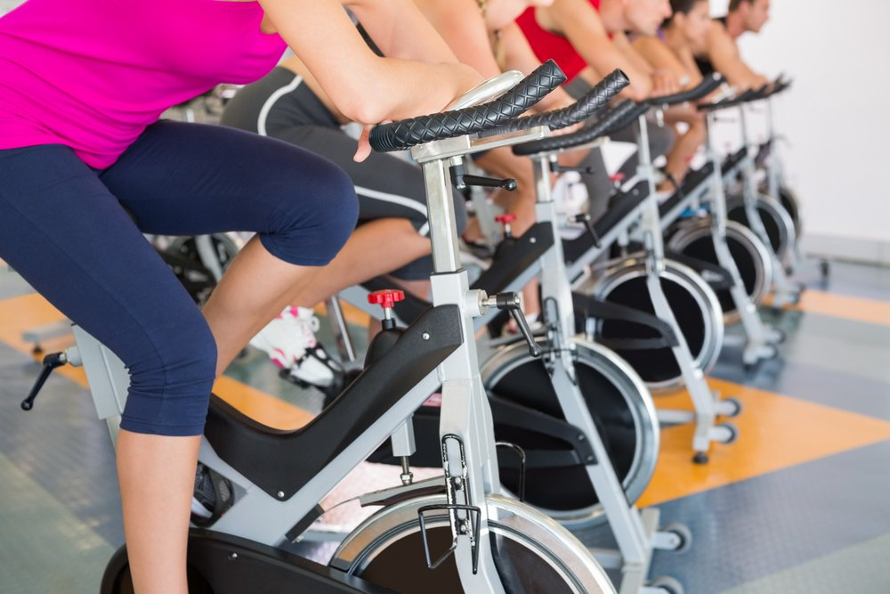 Benefits of cardio shown by a spin class working out in a row.