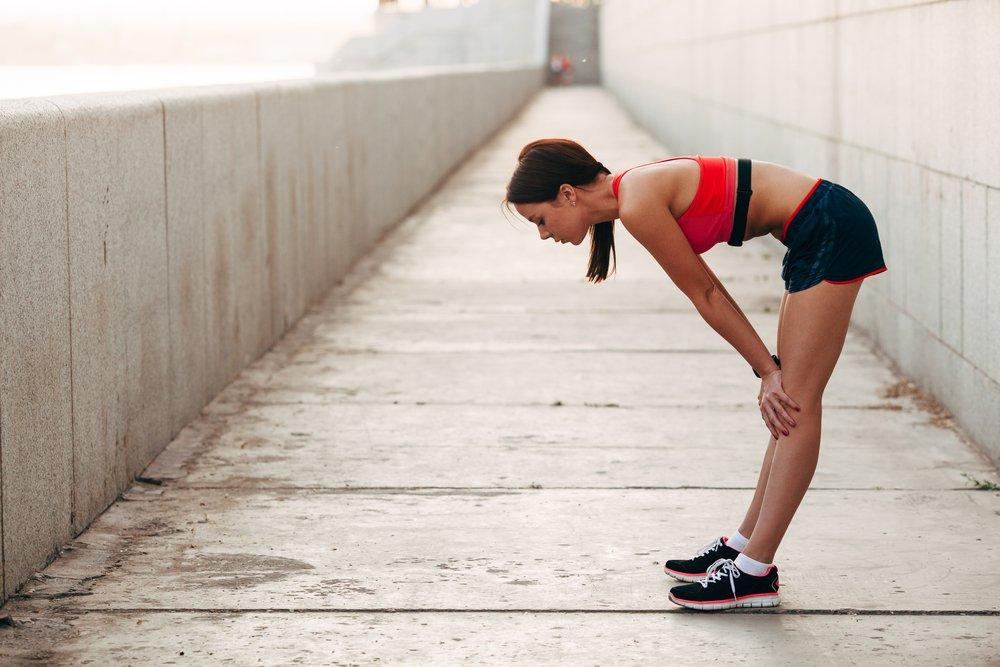 A young woman bent over, catching her breath after hitting the wall whilst running