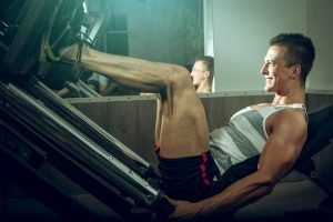 A fit man using a leg press machine in a gym. Exercises like this are good to train your legs