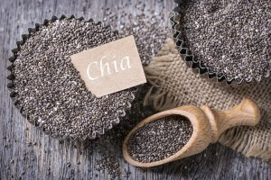 Chia seeds in a metal tart tin on a wodden table with another scoop of chia seeds
