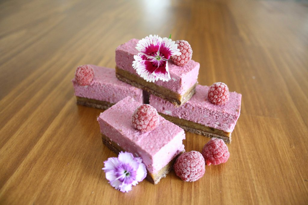 Raspberry Mousse Protein Slice on a wooden table top with frozen raspberries and flowers